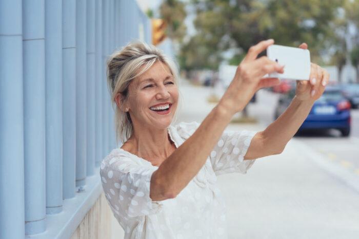 Megatrend Demografischer Wandel: Attraktive Best-Agerin schießt mit ihrem iPhone ein Selfie.